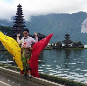 a guy showing off his dress at the Pura Ulun Danu Bratan