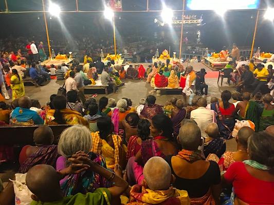 Persone sedute sugli scalini che assistono alla cerimonia del Ganga Aarti al Dashashwamedh Ghat